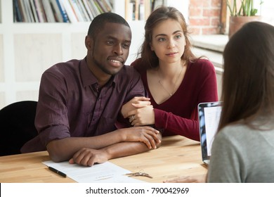 Multiethnic couple considering investment real estate purchase consulting realtor, interracial family listening attentively to mortgage broker thinking of getting bank loan for buying new home house