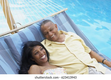 Multi-ethnic couple laying in hammock at poolside