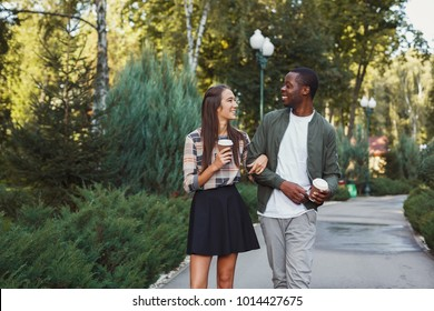 Multiethnic couple in love. Young african-american man and asian woman walk in park and having coffee, copy space