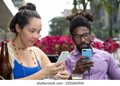 Multiethnic couple at outdoor table in restaurant or bar drinking and using cell phone.