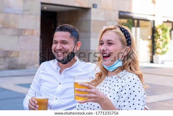 multiethnic couple smiling, laughing and chatting with friends at the bar, drinking beers and celebrating the end of the lockdown, wearing masks under the chin