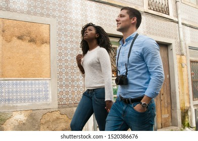Multiethnic couple of tourists going sightseeing. Young man and woman with camera walking in old city street and looking away. Vacation concept