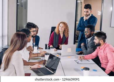 Multiethnic diverse business partners, headed by red-haired caucasian woman, dressed in office trendy wear debating vivaciously during working meeting in conference room.