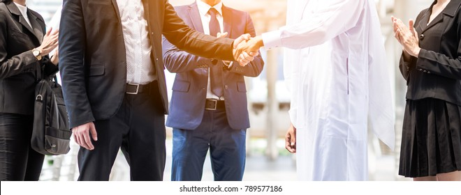 Multi-ethnic and Diverse Business People Shaking Hands. Business deal handshake with Arabic and European ethnic mans.