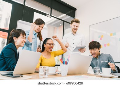 Multiethnic diverse group of coworkers celebrate together with laptop and tablet. Creative team, casual business colleague, college student at modern office. Startup, teamwork, success project concept