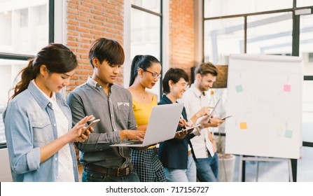 Multiethnic diverse group of happy young adult using information technology gadget devices together. Modern lifestyle culture, casual business, creative people, education, social media network concept