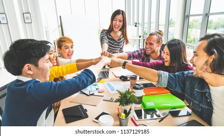 Multiethnic diverse group of office coworker or business partner fist bump in modern office. Colleague partnership teamwork, university student, congratulation event, job or mission accomplish concept