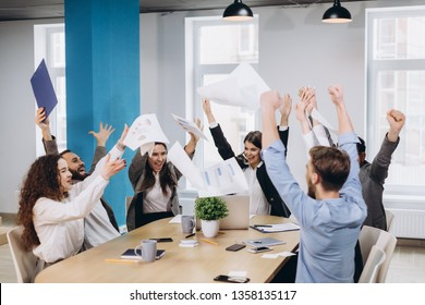 Multiethnic diverse happy team celebrate project success throw paper up together. Corporate community, college graduation, startup activity, salary raise promotion or successful small business concept