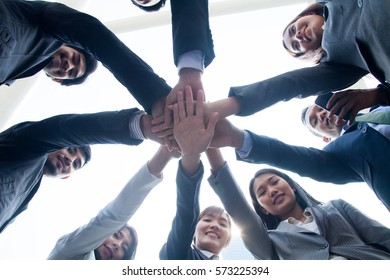 multiethnic ethnic business people putting hand harmonious friendship together,friends with stack of hands showing unity and trust worthy partnership teamwork.team collaborate working with competitors