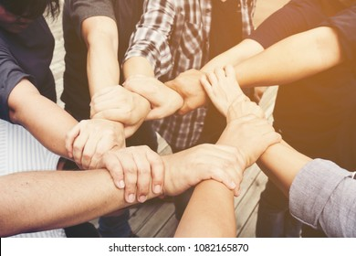 Multiethnic, ETHNIC Group Business PEOPLE at the hands of a Young Businessteam who is a Symbol of their Partnership and Work as a strong Team. Volunteer partner Putting their hands together
