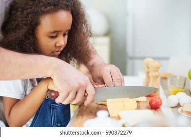 Multi-ethnic family cooking pizza at home: concentrated little girl cutting cheese with the help of her father