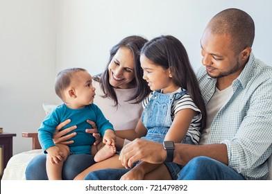 Familia multiétnica jugando con feliz bebé en casa. Los padres y los niños se relajan juntos en el sofá de casa en la sala de estar. Niña sentada en la pierna de papá mirando a su nuevo lindo hermano.