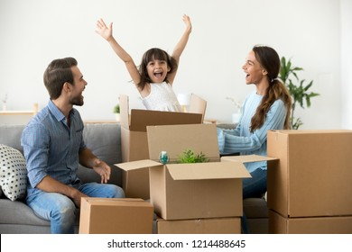 Multi-ethnic family sitting on couch in living room funny daughter jumping out of carton box parents laughing play with child have fun together move at new house. Mortgage loan and relocating concept
