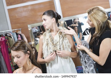 Multiethnic fashion model and female stylist in dressing room
