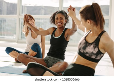 Multi-ethnic females in gym doing high five. Group of young women making high five gesture in gym after successful fitness class after training.
