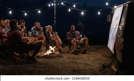 Multiethnic friends chilling around bonfire in campsite and watching movies on screen in night time with glowing garlands above