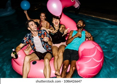 Multi-ethnic friends having fun at party in swimming pool. Happy men and women chilling on air mattress in pool and playing with balloons.