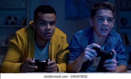 Multiethnic friends playing video games late at night, lazy college students