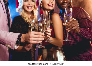 multiethnic friends in santa hats clinking with champagne glasses on new year party