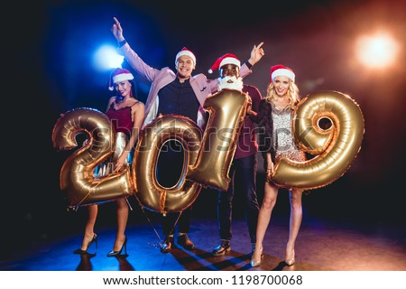 afb7f7984133b multiethnic friends in santa hats holding 2019 new year golden balloons on  black with backlit
