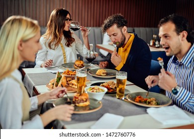 Multiethnic friends sitting at restaurant, drinking alcohol, chatting and having burgers for dinner.
