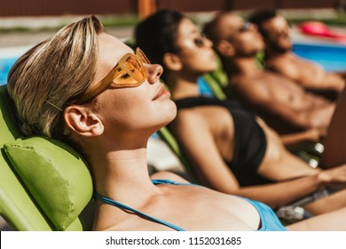 multiethnic friends in sunglasses sunbathing on sunbeds at poolside, selective focus