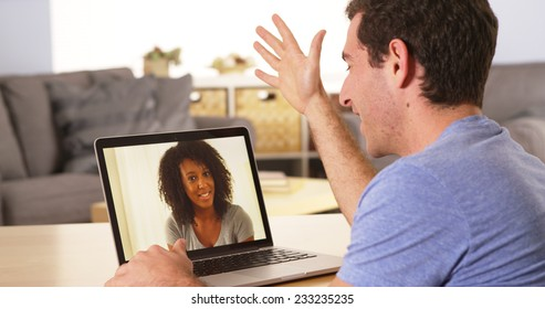 Multi-ethnic friends webcamming on laptop