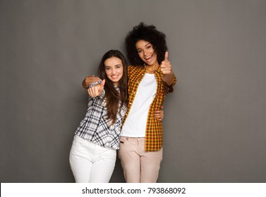 Multiethnic friendship and support concept. Diverse girls hugging and showing thumbs up gesture, having fun at gray studio background with copy space