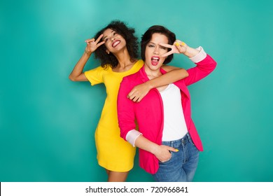 Multiethnic friendship and support concept. Mulatto and caucasian girls in colorful casual clothes hugging and having fun at blue studio background with copy space