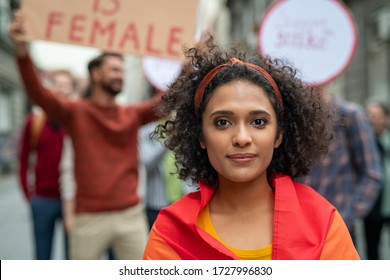 Multiethnic girl at woman empowerment strike on street. Portrait of mixed race girl in rally to protest on equality looking at camera. Multiracial woman in march fighting for freedom and lgbt rights.