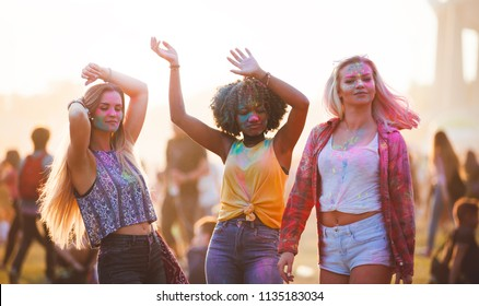 Multiethnic girls covered in colorful powder dancing and celebrating summer holi festival