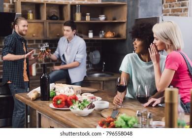 multiethnic girls gossiping about male friends in kitchen