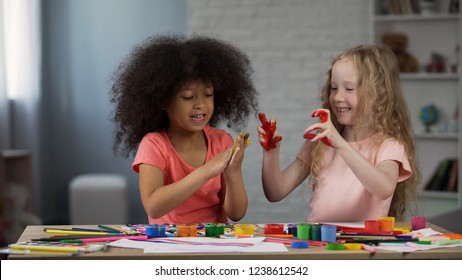 Multi-ethnic girls at kid club, sitting at table and smudging hands with paints