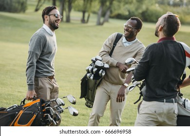 multiethnic golf players with golf clubs having fun on golf course