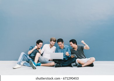 Multiethnic group 4 men celebrate together using laptop computer, sit by blue wall with copy space. College student, information technology gadget, education, social network, or success concept.