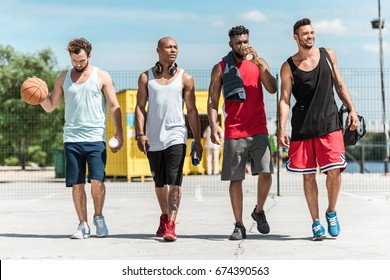multiethnic group of athletic basketball players walking on court