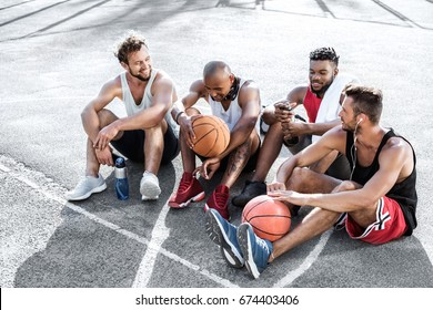 multiethnic group of basketball players resting on court together