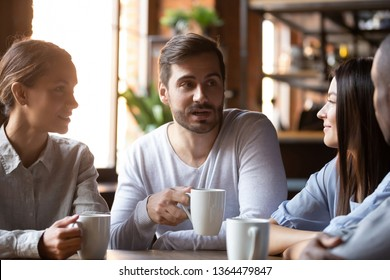 Multi-ethnic group of best friends millennial girls and guys chatting sitting in cafe, employees colleagues during lunch gathered in cafeteria talking drinking tea, communication good relation concept