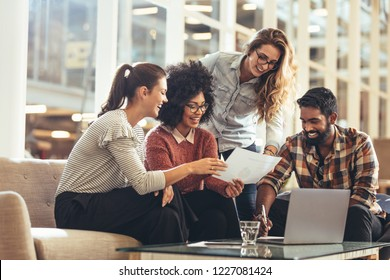 Multiethnic group of business people working together in office. Businessman sitting with female colleagues discussing work.