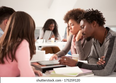 Multiethnic group of cheerful college students studying together.