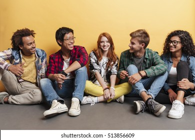 Multiethnic group of cheerful young friends talking and laughing over yellow background