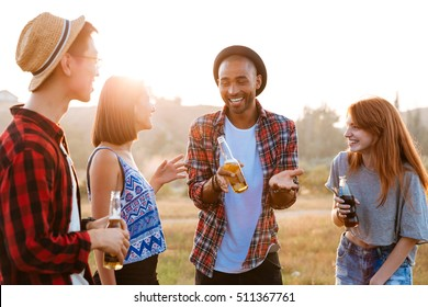 Multiethnic group of cheerful young people with beer and soda talking and laughing outdoors