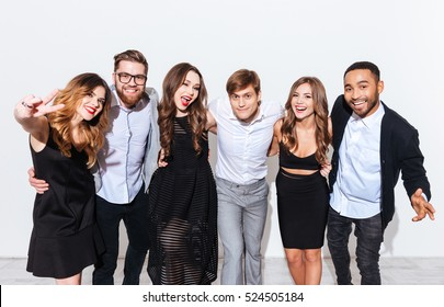 Multiethnic group of cheerful young people standing and having fun together over white background