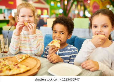 Multi-ethnic group of children eating pizza enjoying awesome birthday party in cafe, all looking at camera