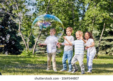 Multi-ethnic group of children having fun with big soap bubbles while spending warm summer day at public park illuminated with sunbeams