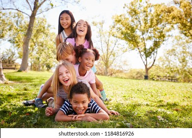 Multi-ethnic group of children lying in a pile in a park