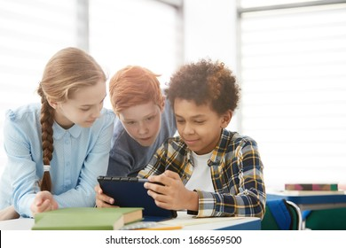 Multi-ethnic group of children using digital tablet or internet while sitting together at desk in school classroom copy space