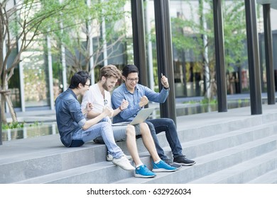 Multiethnic group of college students or asian freelance coworker using using laptop with happy and celebrate action. Lifestyle with information technology gadget, education, or social network concept