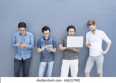 Multiethnic group of college students or asian freelance coworker using smartphone and laptop computer together. Lifestyle with information technology gadget, education, or social network concept