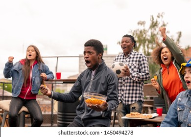Multi-ethnic group of ecstatic youth with snack shouting during broadcast